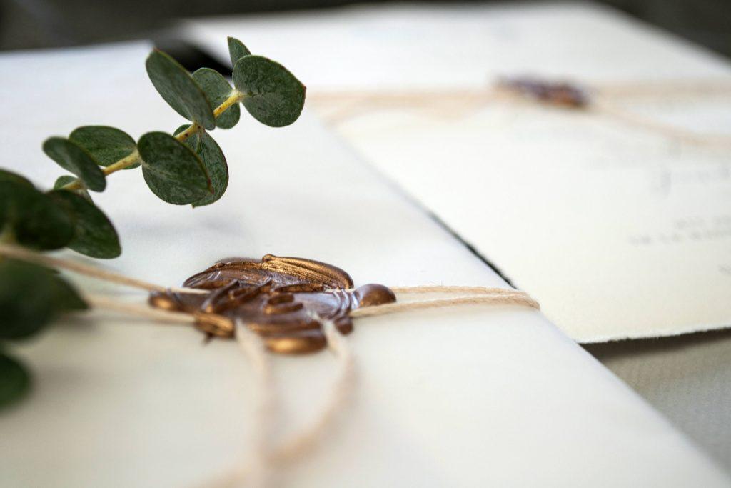 Nahaufnahme eines Wachssiegels mit Eucalyptuszweig zur Hochzeit.