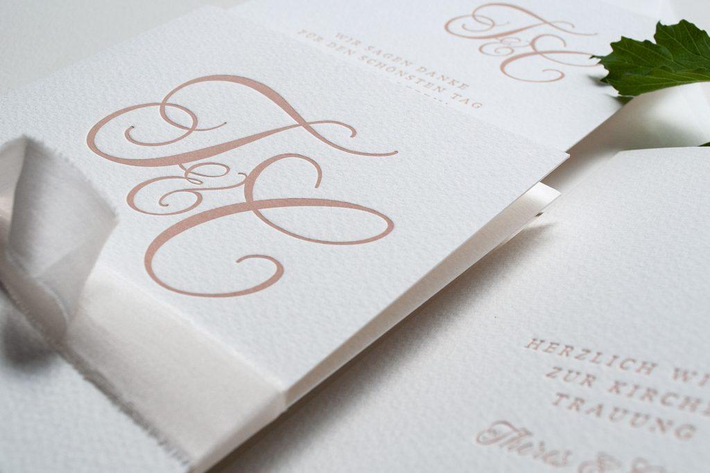 Nahaufnahme Monogramm Hochzeitspapeterie im Letterpress in Pudertönen, Blush Einladung und Dankeskarte.